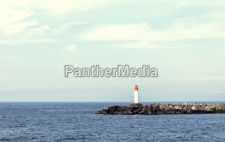white lighthouse and stone pier