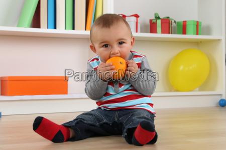 baby eating an orange fruit