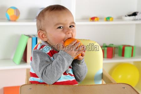 baby child eating an orange fruit
