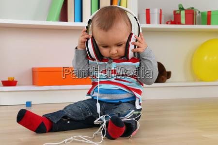 dziecko slucha muzyka przez helmofonow