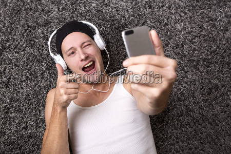 attractive man with headphones makes selfie