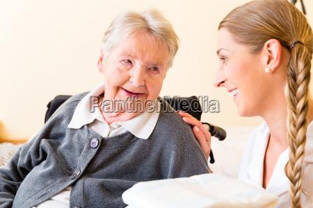 nurse brings towels to senior in
