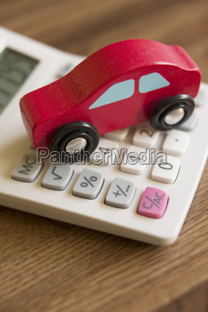 red toy wooden car on calculator