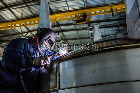 man welding with reflection of sparks