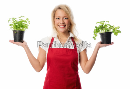 woman with apron presenting basil and