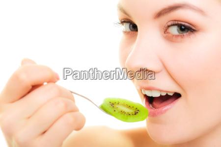 girl eating slices of kiwi fruit