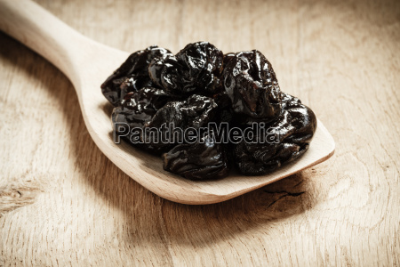 dried prunes plums on wooden spoon