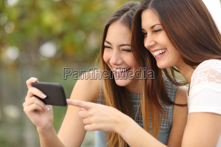 two funny women friends laughing and