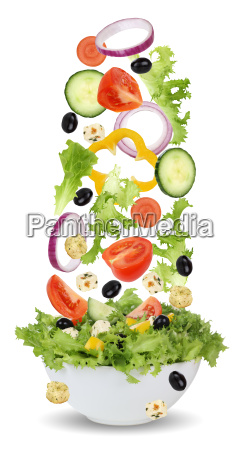 filling salad ingredients in bowl with