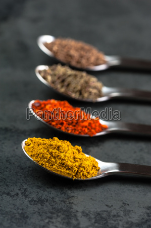 spoons with spices on a slate