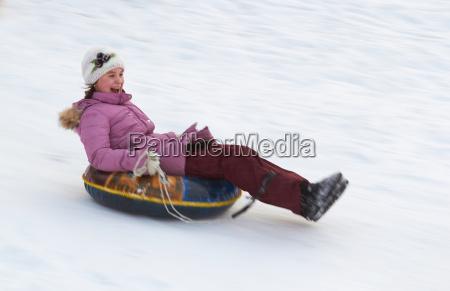 happy teenage girl sliding down on
