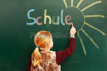 girl writes on the blackboard