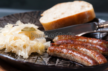 roast sausages with sauerkraut in a