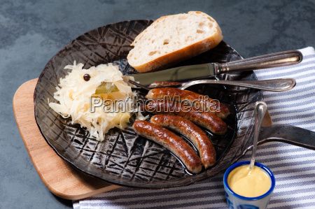 sausages with sauerkraut in a pan