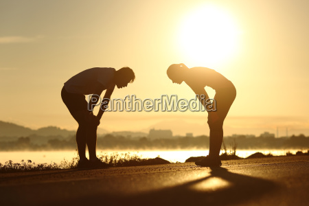 exhausted and tired fitness couple silhouettes