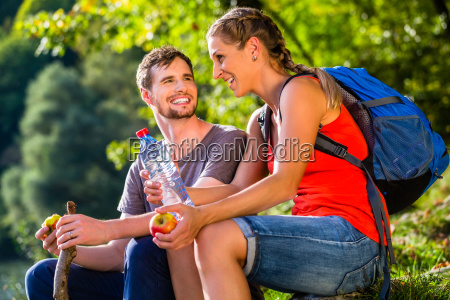 couple in hiking in summer drinks