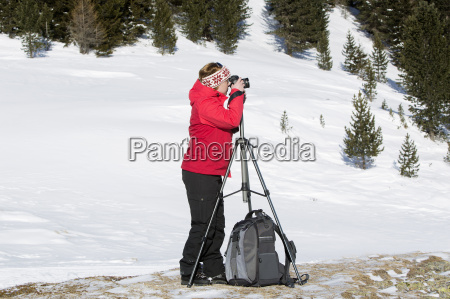 female photographer takes pictures in winter