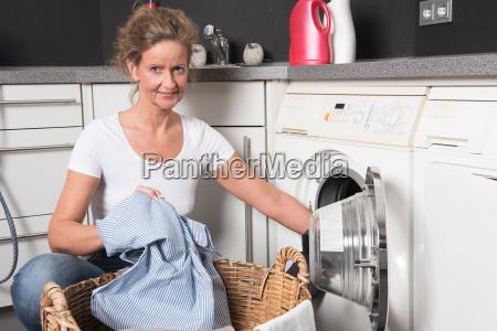 woman loads washing machine