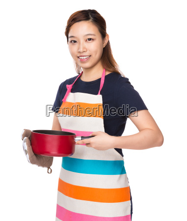 asian housewife holding saucepan with oven