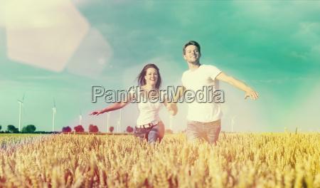 happy couple running on romantic kornfeld