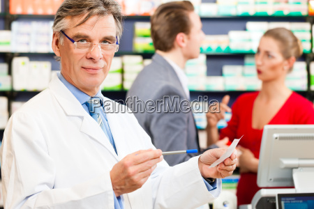 pharmacist, in, his, pharmacy, with, customers - 13620010