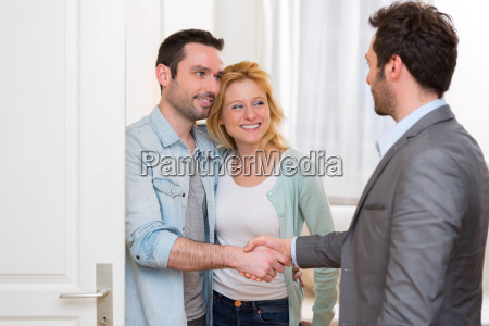 young happy couple handshaking real estate