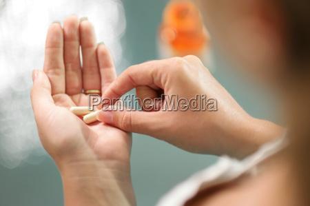 young woman taking vitamins ginseng pill