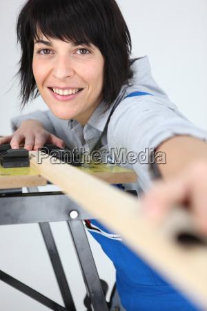 female carpenter taking measurements