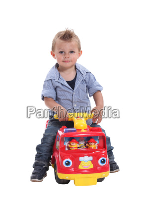 little, boy, playing, on, toy, car - 13660546