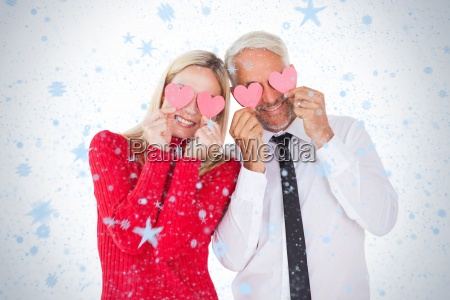 silly couple holding hearts over their