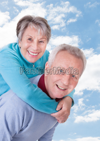 senior couple enjoying piggyback ride