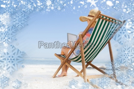 woman in sunhat sitting on beach