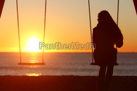 single woman alone swinging on the