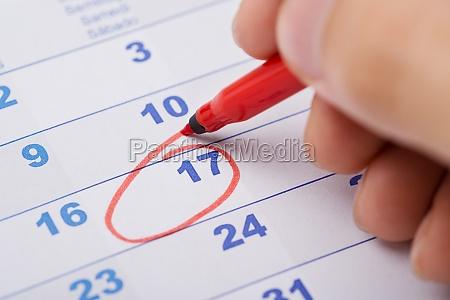 hand marking 17th date on calendar