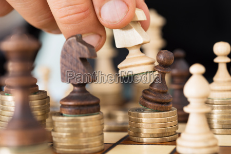 hand playing chess stacked on coins
