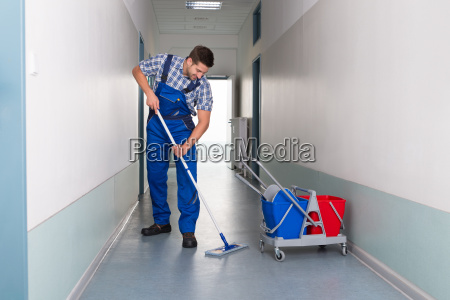 male worker with broom cleaning office