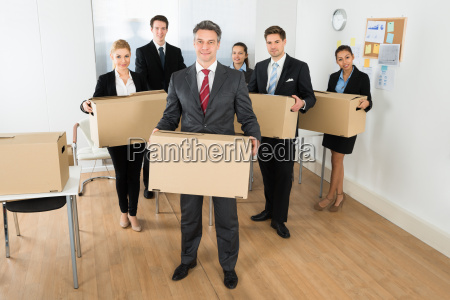 employees in office holding cardboard boxes