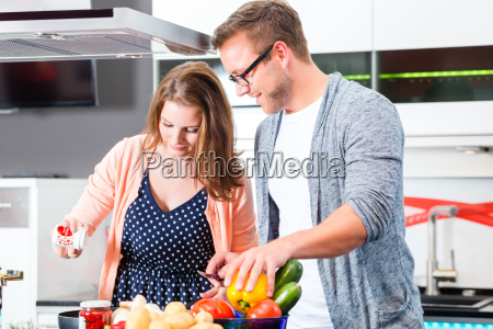 couple cooking pasta at home in