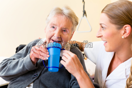 nurse gives old woman tea to