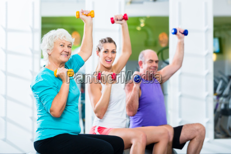 seniors and trainers with dumbbells in