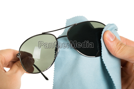 person cleaning sunglasses