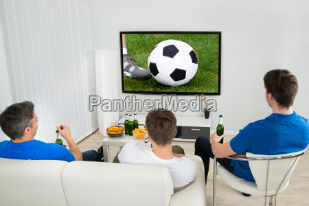 three men watching soccer match