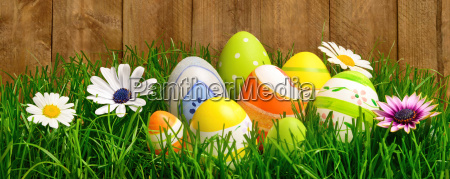 easter decoration in grass against wooden