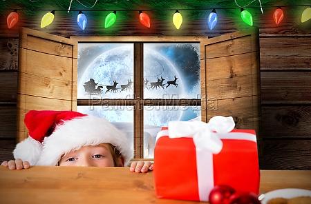 composite image of festive boy peeking