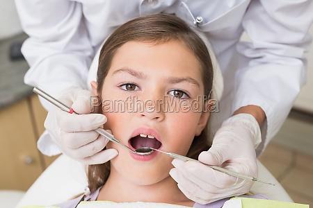 pediatric dentist examining a patients teeth