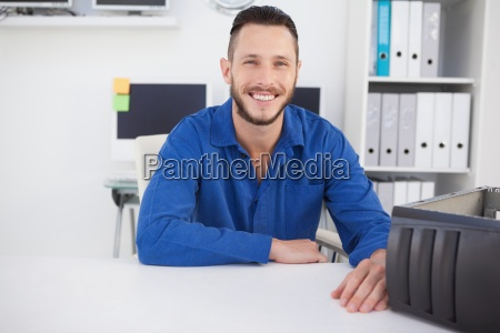 computer engineer sitting at desk smiling