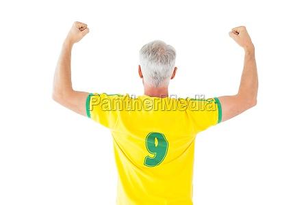 brazilian football fan in yellow cheering