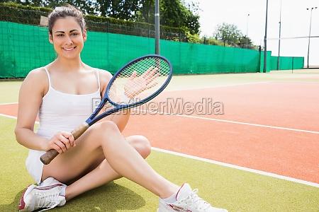 pretty tennis player sitting on court