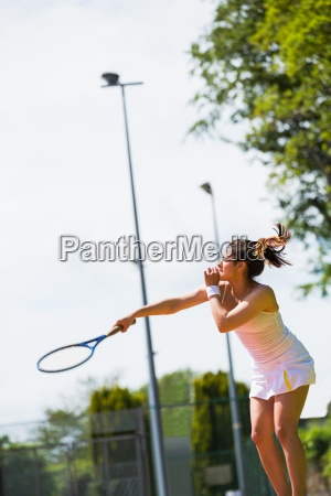 pretty tennis player about to serve