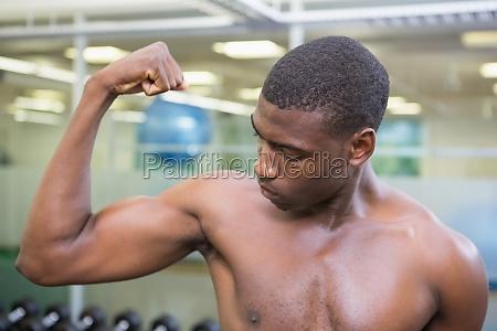 shirtless muscular man flexing muscles in